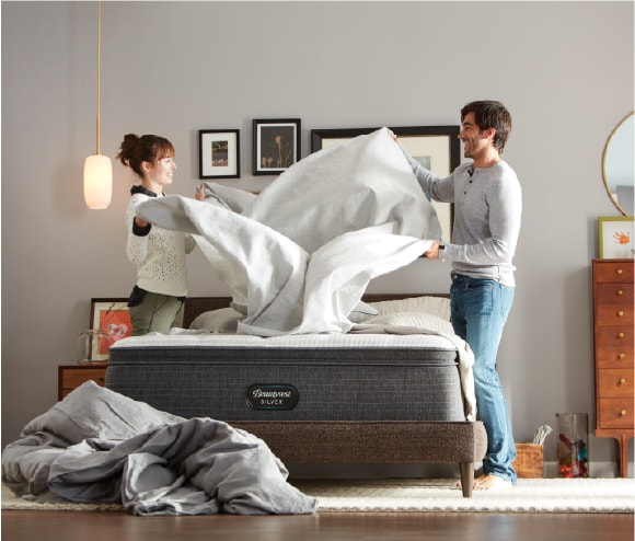 couple making bed beautyrest mattress